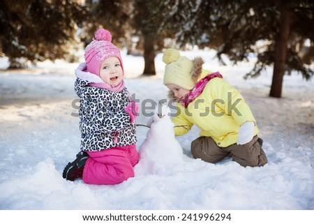 two little girls make a snowman - stock photo