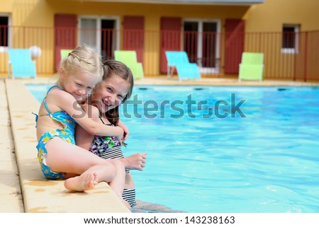 two little girls  near the open-air swimming pool