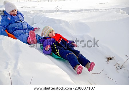 Two little girls on a sled sliding down a hill on snow in winter
