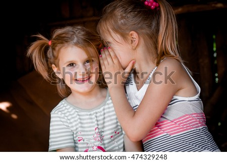 Two little girls one telling a secret to another
