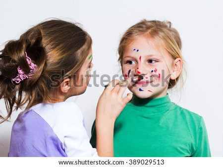 Two little girls painting and have a fun