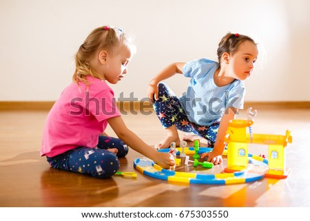 Two little girls play with friends and have fun
