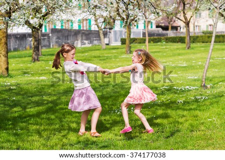 Two little girls playing in spring garden on a nice sunny warm day, wearing skirts - stock photo