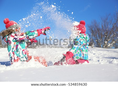 two little girls playing  on snow in winter time