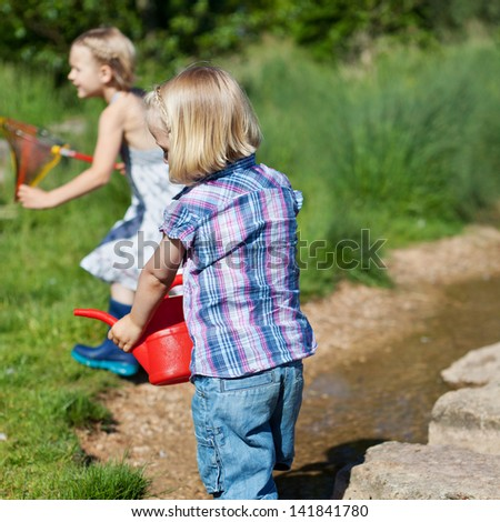 Two little girls playing outdoors on the shore of a lake running around with a plastic watering can and fishing net