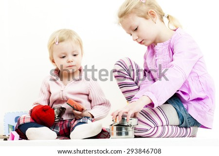 two little girls playing with child dish