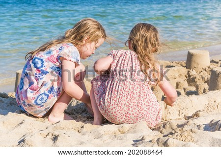Two little girls playing with sand on the seashore - stock photo
