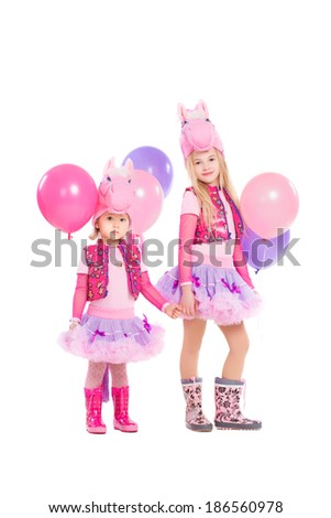 Two little girls posing in pink pony suit. Isolated on white - stock photo