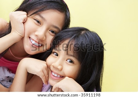 Two little girls posing to camera together happily - stock photo