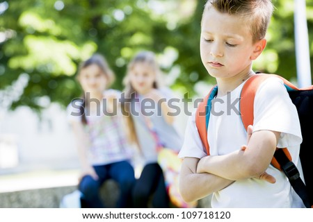 Two little girls potning at the little sad boy, focus on foreground - stock photo