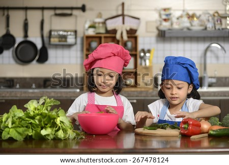 Two little girls, preparing healthy food, in the kitchen - stock photo