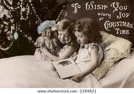 Two little girls reading a bettime story - a 1909 vintage hand-tinted photo greeting card - stock photo