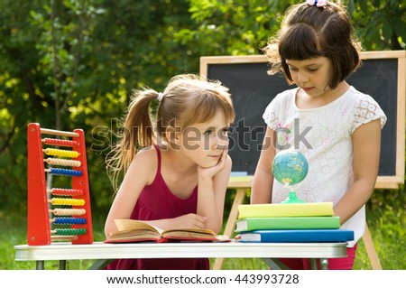 Two little girls reading a book on the nature and talking