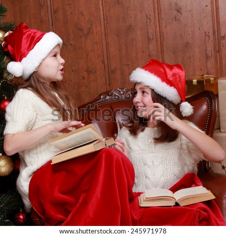 Two little girls reading in a book near the christmas tree  - stock photo