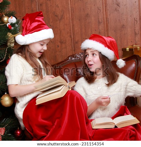 Two little girls reading in a book near the christmas tree on Holiday theme/Charming kids reading books on Christmas time - stock photo