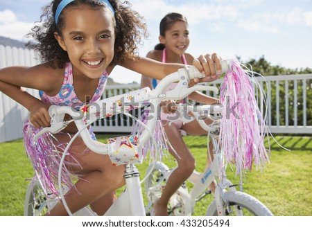 Two little girls riding on bicycle - stock photo