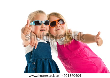 two little girls showing thumbs up. Studio shot. - stock photo