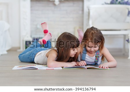 two little girls sisters reading a book lying on the floor - stock photo