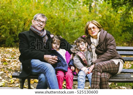 Two little girls sit in the autumn park with her grandparents on a bench