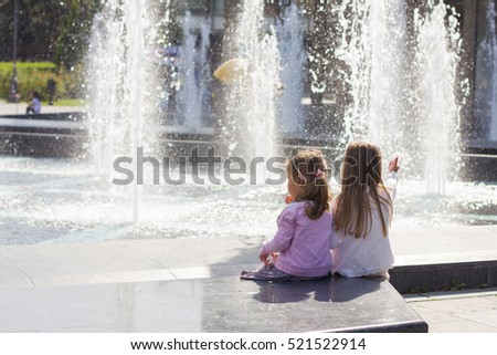 Two little girls sitting at city fountain, enjoying summer day.
