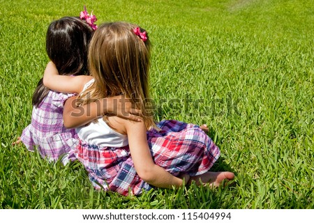 Two little girls sitting on grass - stock photo