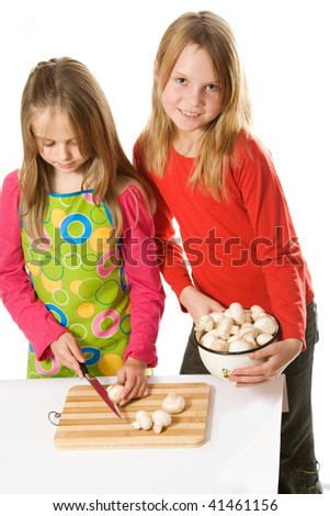 Two little girls slicing mushrooms. Isolated - stock photo