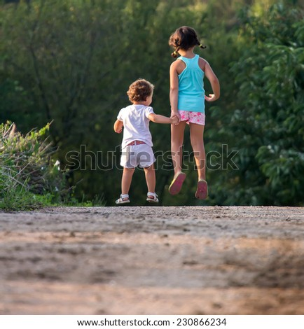 Two little girls strolling through the countryside