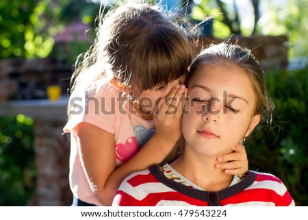 Two little girls telling secrets