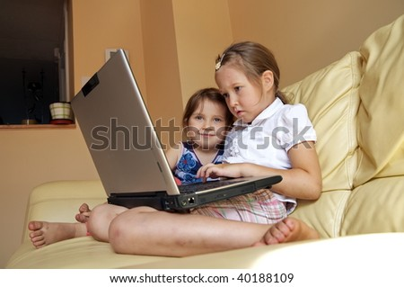 Two little girls using laptop at home