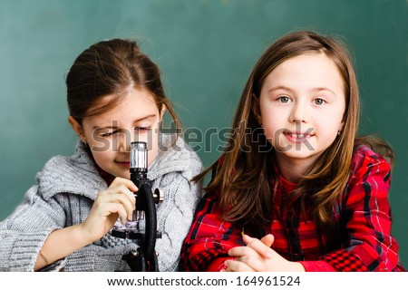 Two little girls using microscope in the classroom - stock photo