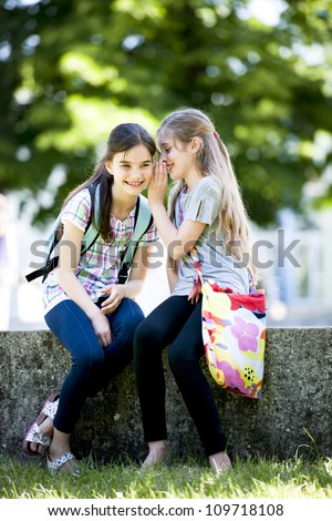 Two little girls whispering secrets while sitting outdoors - stock photo