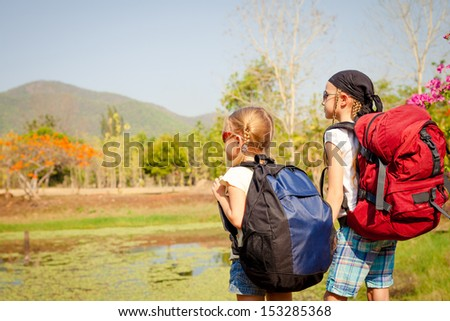 two little girls with backpack walking on the road