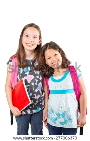 Two little girls with backpacks on their way to school - stock photo