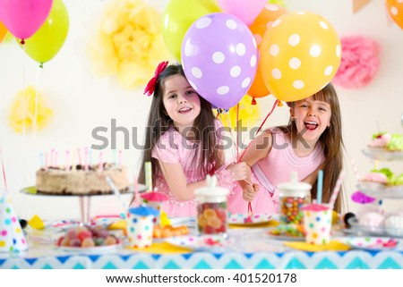 Two little girls with balloons having fun at birthday party