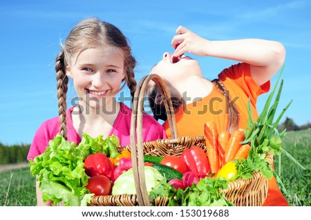 Two little girls with basket of vegetables - stock photo