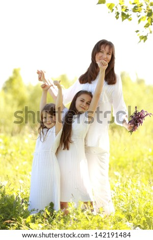 Two little girls with her mother walking in the summer park on the green grass at sunset - stock photo