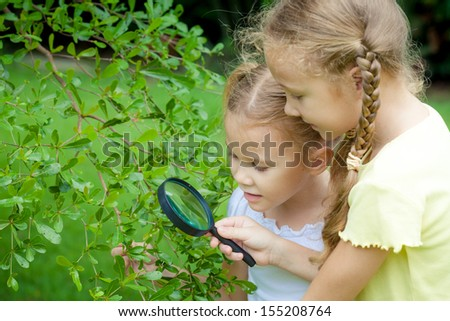 Two little girls with magnifying glass outdoors in the day time - stock photo