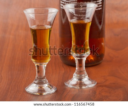 Two little glasses of whisky near a bottle with black label (focus on the glass on the left) - stock photo