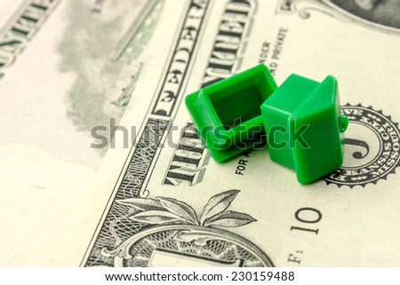 two little green houses made of plastic are laying on their roofs on dollar banknotes, business concept - stock photo