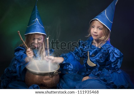two little halloween witches with cauldron - stock photo