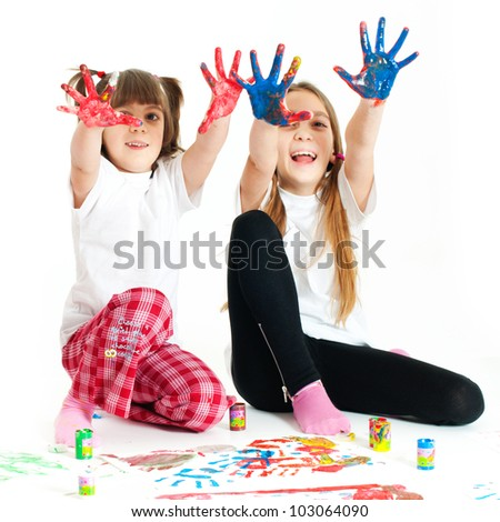 Two little happy beautiful girls (sisters) painting on white background