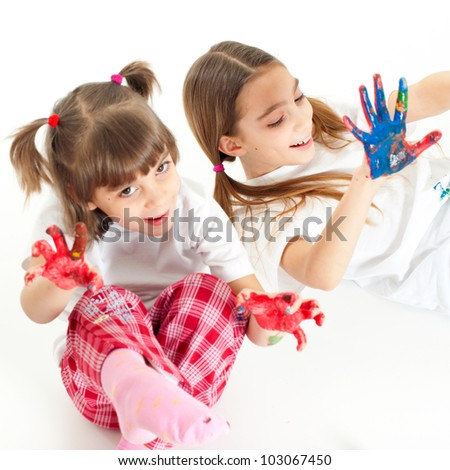 Two little happy beautiful girls (sisters) playing with finger colours on white background
