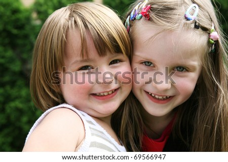 Two little happy girls playing together outdoor.