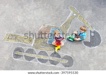 Two little happy kid boys having fun with excavator picture drawing with colorful chalk. Creative leisure for children outdoors in summer. - stock photo