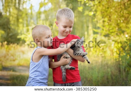 Two little happy kids playing with cat  in summer park - stock photo