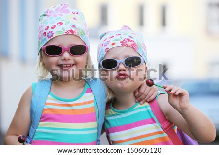 Two little identical twin girls with their blond hair tied up in bandannas and wearing sunglasses smiling happily at the camera - stock photo