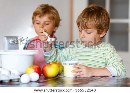 Two little kid boys baking apple cake in domestic kitchen. Adorable siblings having fun with working with mixer, eggs and fruits. Twins helping at home - stock photo