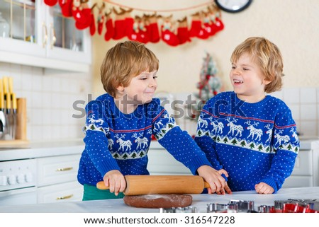 Two little kid boys baking gingerbread cookies. Happy siblings, children in blue xmas pullovers. Kitchen decorated for Christmas. Family, holiday, kids lifestyle concept. - stock photo