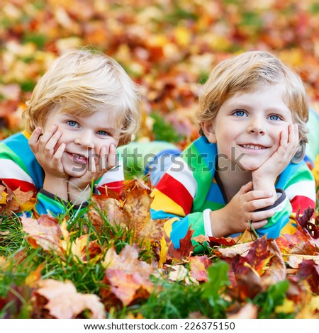 Two little kid boys lying in autumn leaves in colorful clothing. Happy siblings having fun in autumn park on warm day. Square format. - stock photo