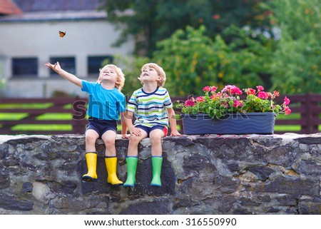 Two little kid boys sitting together on stone bridge in european village. Happy family of two. Twins in colorful gumboots, outdoors.